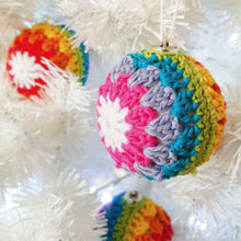 Crochet rainbow stripe bauble hanging on a Christmas tree.