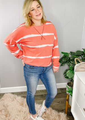 Coral striped top with long sleeves, medium weight material and front stitch details.