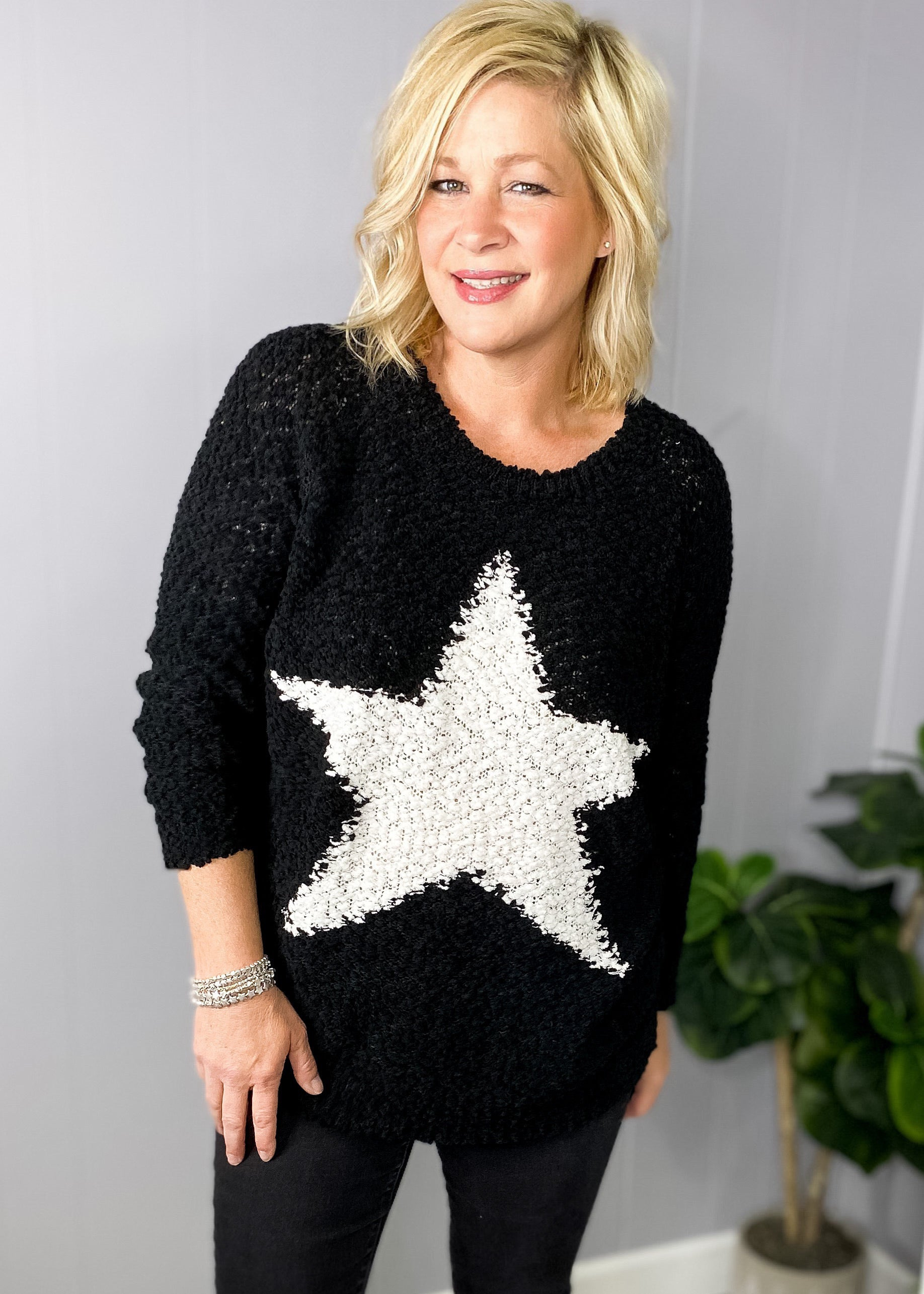 Black popcorn sweater with white star at L.E & CO Boutique.