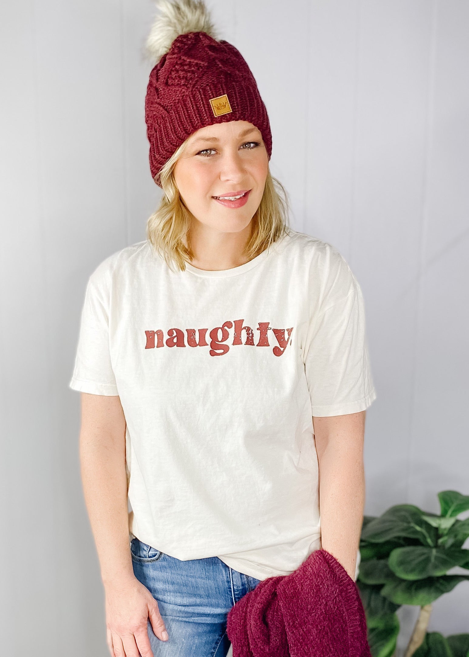 Naughty holiday tee in cream with dark red print. Available in small-x large