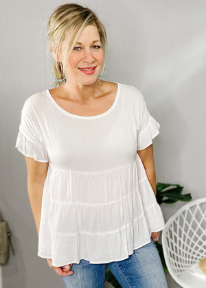 Our Tiered babydoll top features a lightweight material with tiered body and a light soft ruffle sleeve.