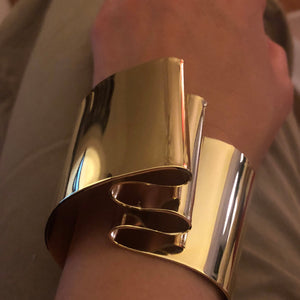 "This is our classic, timeless cuff, and one of our best sellers. The folds evoke Richard Serra. It's an empowering design you'll keep coming back to in your jewelry box!  Cuff is hand formed using a 1mm thick sheet that is 1.5"" wide. Piece usually is 1/2"" above your wrist.  Bracelet is made in brass and finished in 14k gold, nickel free plating."