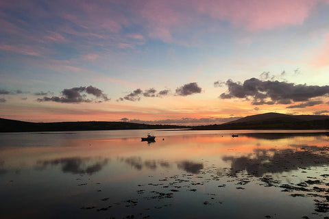 Sunset view of Smerwick Harbour in the Dingle Peninsula with the sea and dark mountains outlined in the distance