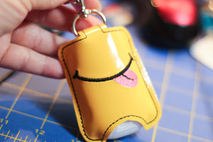 Smiley Face with Tongue Hand Sanitizer Holder Snap Tab Version In the Hoop Embroidery Project 1 oz BBW for 5x7 hoops