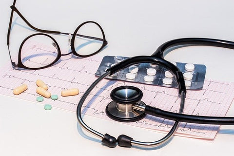 pills and doctor's stethoscope and glasses