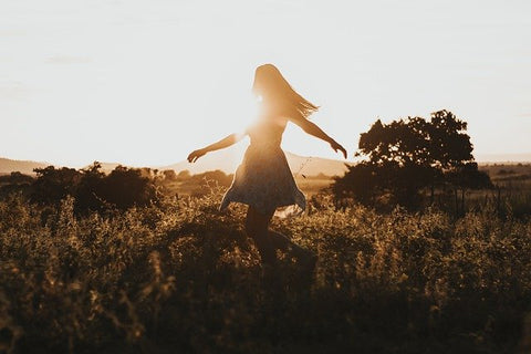 woman happily twirling in a field