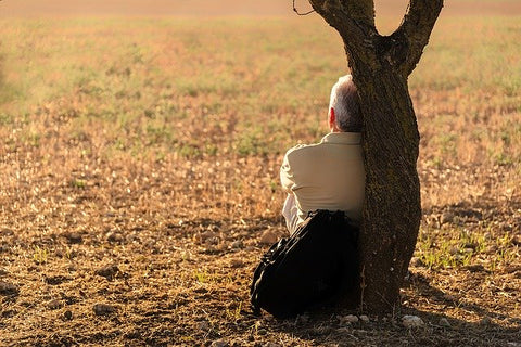 man sitting up against a tree - taking a break