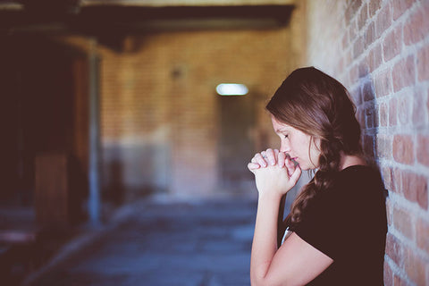 woman praying against a brick wall