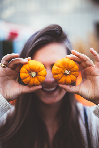 Woman holding two small pumpkins up to cover her eyes