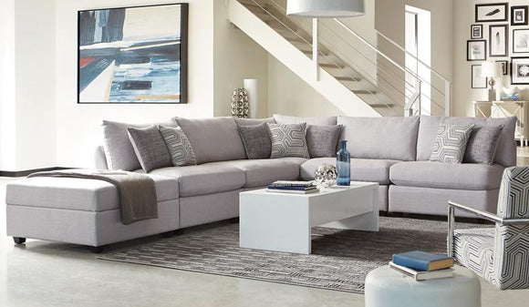 Scott Living sectional sofa in living room with decorative pillows and paintings