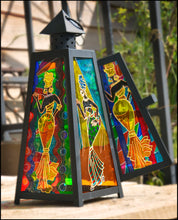 A black candle lantern in a pyramid shape with brightly coloured glass showing 4 African dancers against an Ankara background