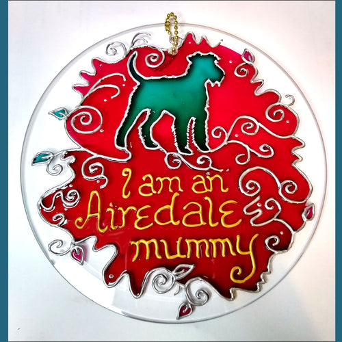 "A six inch hanging glass suncatcher, hand painted in pink & silver, with a turquoise dog & the text ""I am an Airedale mummy"""