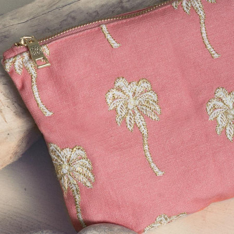 Image of Soft canvas travel pouch with embroidered Palmier or palm tree pattern in coral colour on beach