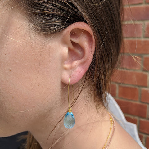 Image of Arabella wishbone drop earrings with teardrop blue quartz gemstone on model