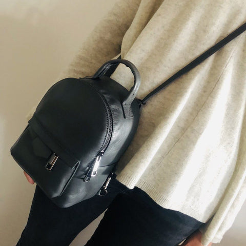 Modern genuine Italian leather mini convertible crossover backpack in black on model as cross body bag