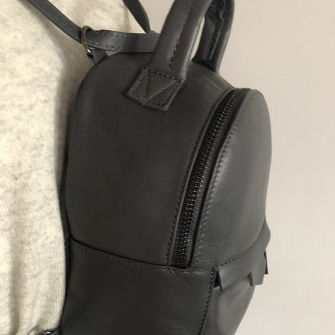 Modern genuine Italian leather mini convertible crossover backpack in black on model as rucksack - close up