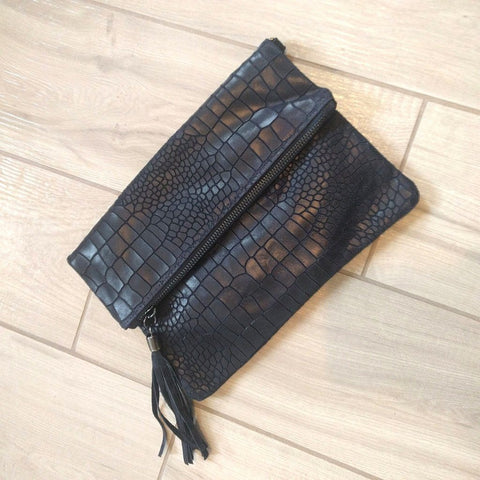 Crocodile hide effect foldover Italian leather clutch bag in navy on a tiled background