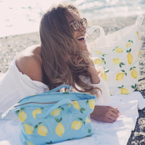 Image of Soft canvas travel bag with Lemon pattern in chambray or baby blue colour - on beach with model