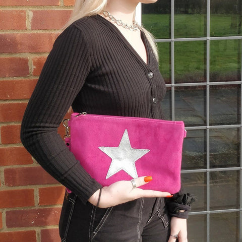 Image of Italian suede leather clutch bag with shiny metallic leather star in magenta with a model