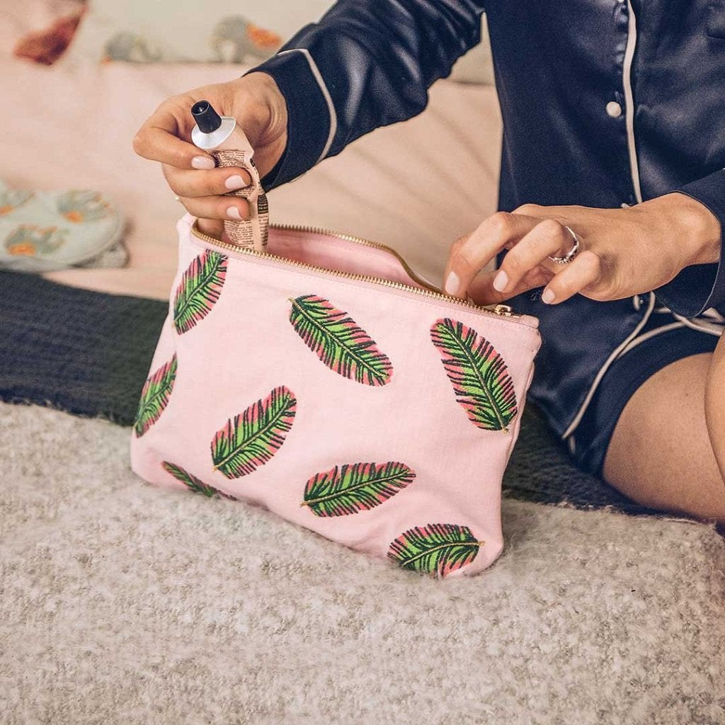 Soft canvas travel pouch in pink rose Tropical Banana Leaf pattern with model