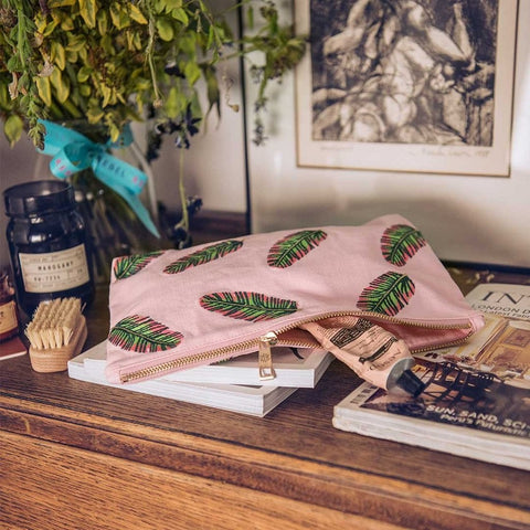 Image of Soft canvas travel pouch in pink rose Tropical Banana Leaf pattern on table
