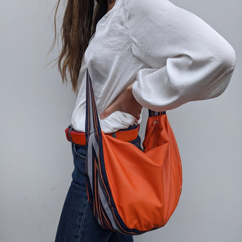 Image of Band shoulder bag in soft orange leather on model