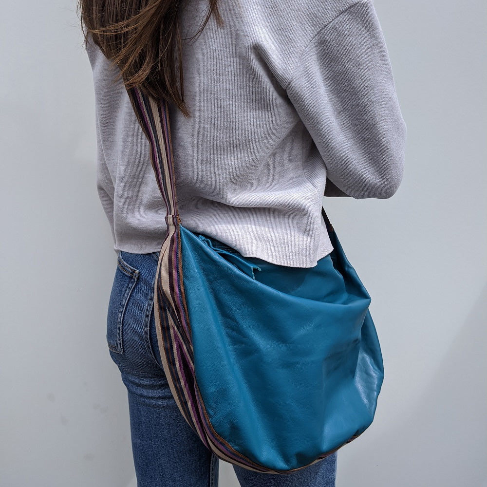 Band shoulder bag in soft turquoise leather on model