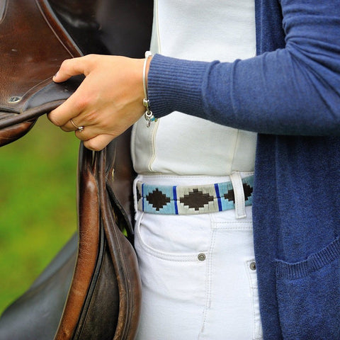 Argentinian embroidered bridle leather Polo belt in brown leather with pale blue, white & blue stripe on a model