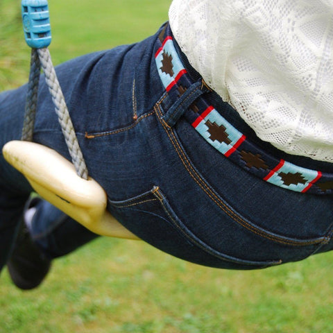 Narrow Argentinian embroidered bridle leather Polo belt in brown leather with navy, pale blue & red stripe on model