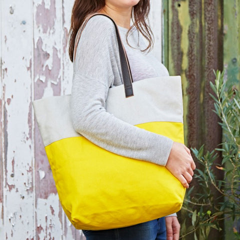 Bright handmade canvas shopper bag in yellow & mushroom with comfortable leather handle on a model