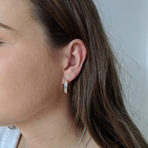Small chunky sterling silver hoop earrings on a model
