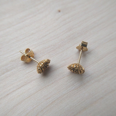 Detailed dainty flower stud earrings selection in gold plate on sterling silver - on wood background