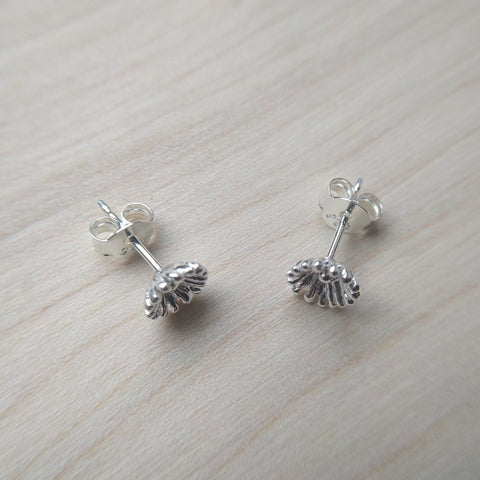 Detailed dainty flower stud earrings selection in sterling silver - on wood background