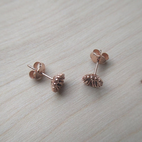 Detailed dainty flower stud earrings selection in rose gold plate on sterling silver - on wood background