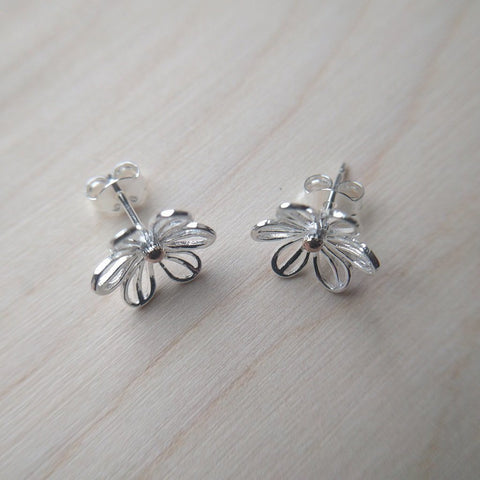 Pretty daisy stud earrings in sterling silver with gold plated central detail on a wood background