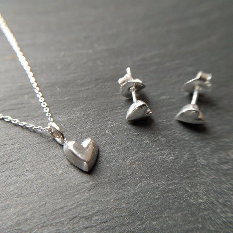 Devotion stud earrings and matching necklace with 3D heart shaped charms in sterling silver - on slate background