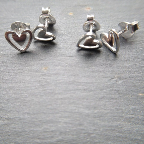 Sterling silver solid heart stud earrings in silver or rose gold plate and with larger silhouettes around the outside