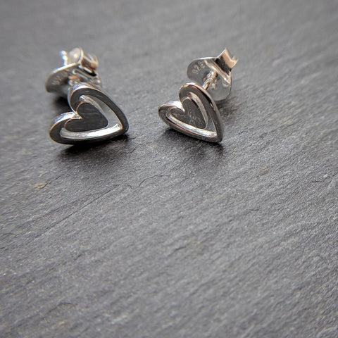 Sterling silver solid heart stud earrings with a larger silhouette around the outside