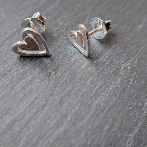 Sterling silver solid heart stud earrings in rose gold plate with a larger silhouette around the outside in silver