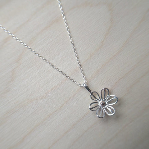 Pretty daisy necklace in sterling silver with gold plated central detail on an adjustable chain - wood background