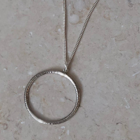 Hammered sterling silver large open circle necklace on a marbled background