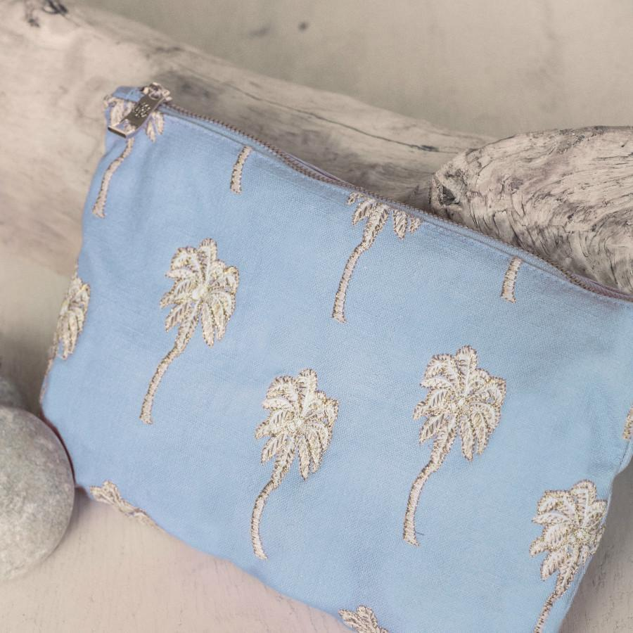 Soft canvas travel pouch with embroidered Palmier or palm tree pattern in baby blue colour on beach