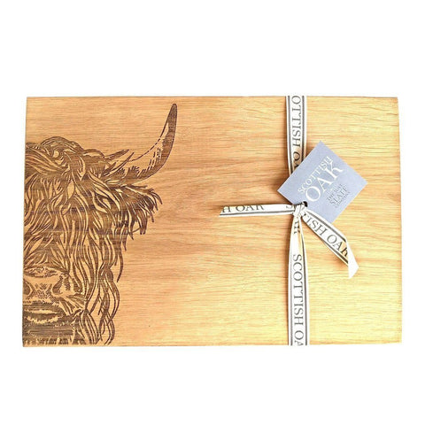 Image of Scottish oak cutting or serving board with engraved highland cow decoration on white background