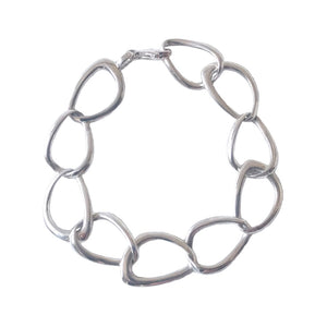 A slightly heavier bracelet in sterling silver with irregular shaped links with a lobster clasp on a white background