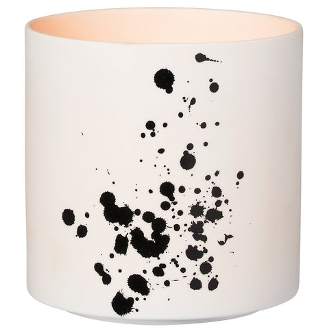Delicate porcelain table light in Nigra Blanka pattern with black dabs by räder with lit tealight