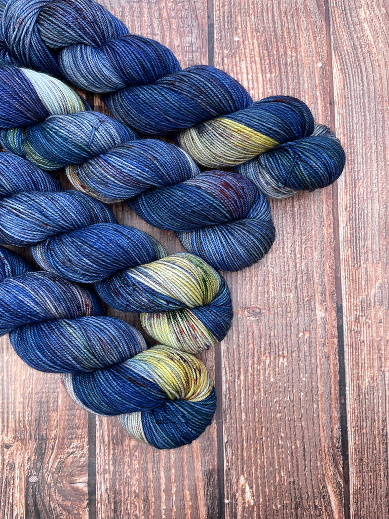 Midnight Crossroads on Gracious Sport. A variegated blue colorway with light yellow, green, and gray accents, speckled with coordinating colors. Four wound skeins shown.