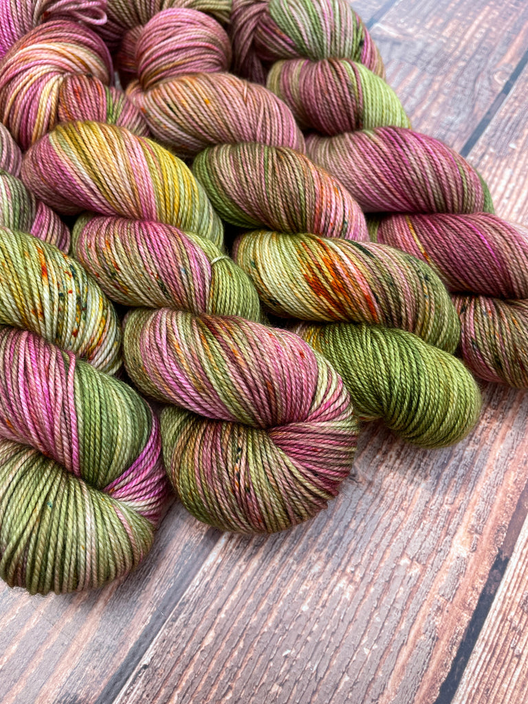 Tea In The Rose Garden on Gracious Sport. A variegated mix of rose, moss green, and a bit of golden yellow with coordinating speckles. Four wound skeins shown.