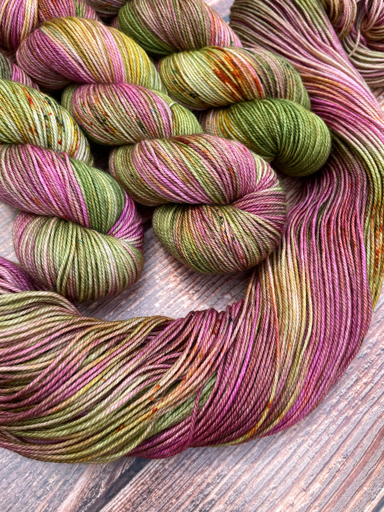 Tea In The Rose Garden on Gracious Sport. A variegated mix of rose, moss green, and a bit of golden yellow with coordinating speckles. Three wound skeins shown with another skein opened to show additional details.
