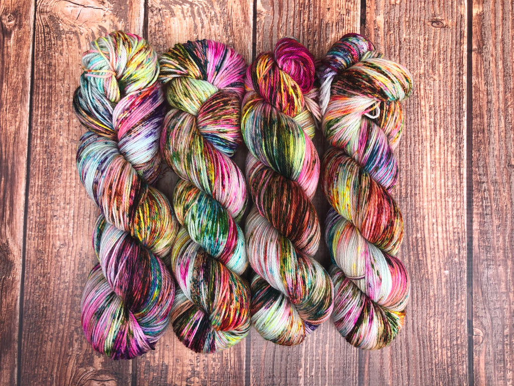 Picture shows four skeins of speckled variegated yarn on a distressed wood background.