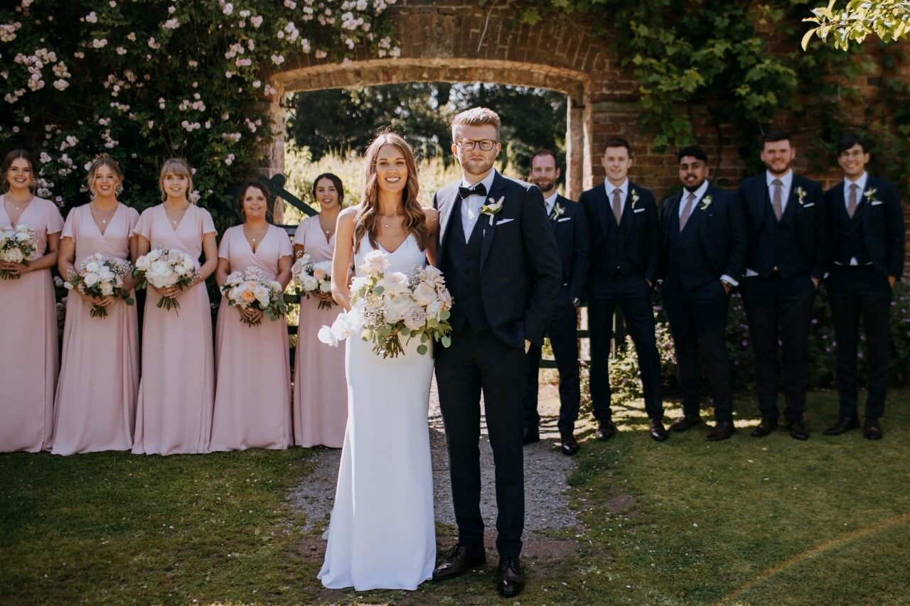 Bride and groom with their bridesmaids wearing pink dresses.